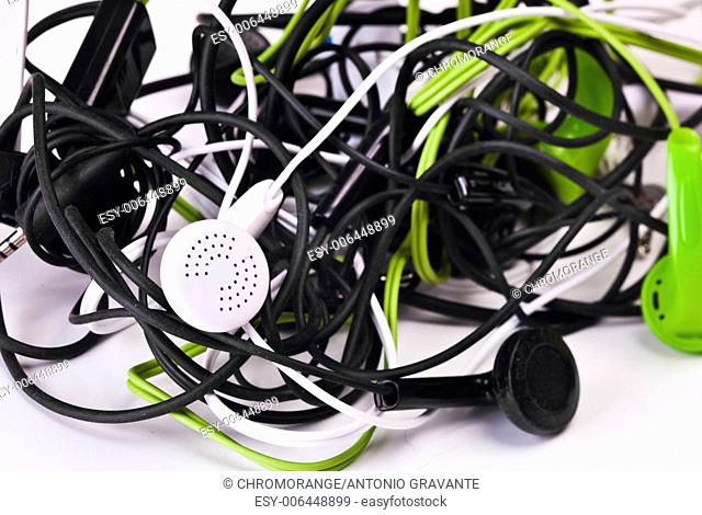 Twisted headphones, of different colors, on white background