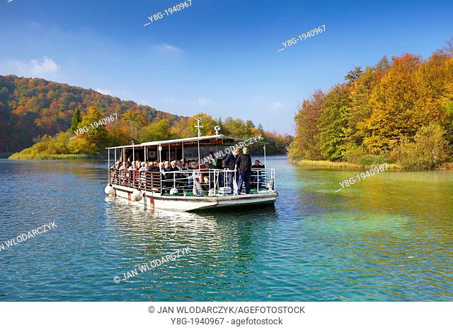 Croatia - autumn landscape of Plitvice Lakes National Park, electric power ferry boat with tourists on the lake, Plitvice, central Croatia