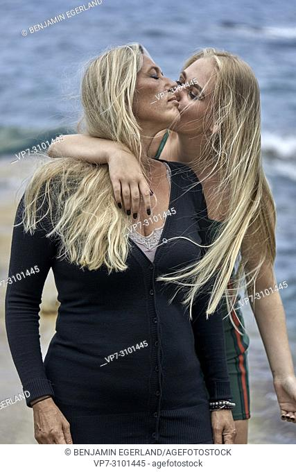 teenage daughter (13 years) kissing mother (43 years) next to sea. Danish ethnicity