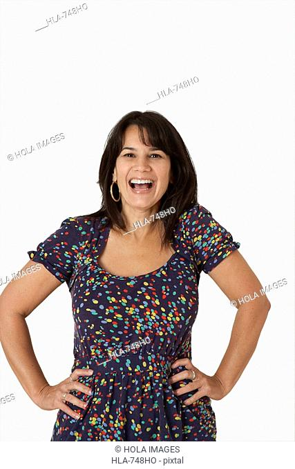 Portrait of a mature woman standing with her arms akimbo and laughing