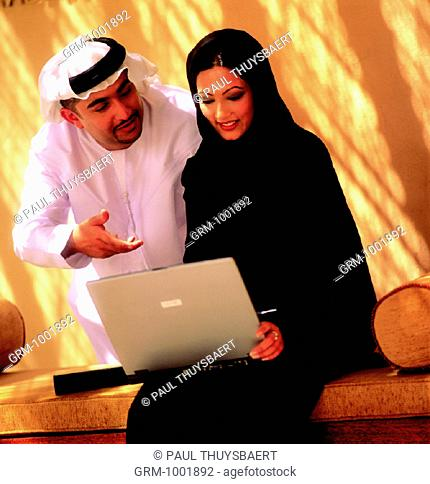 Arab businesspeople using a laptop
