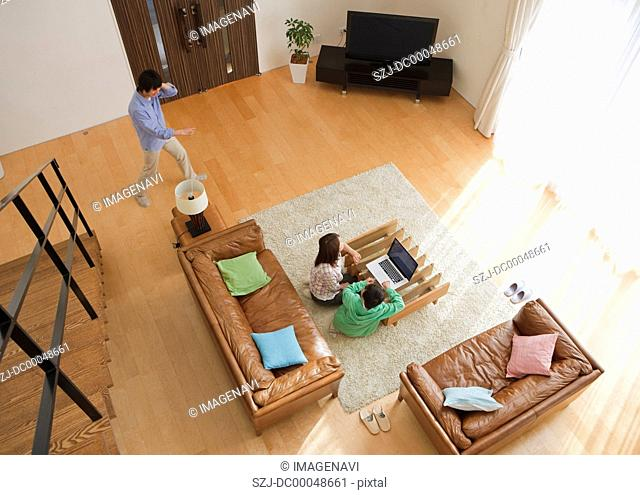Family looking at laptop in a living room