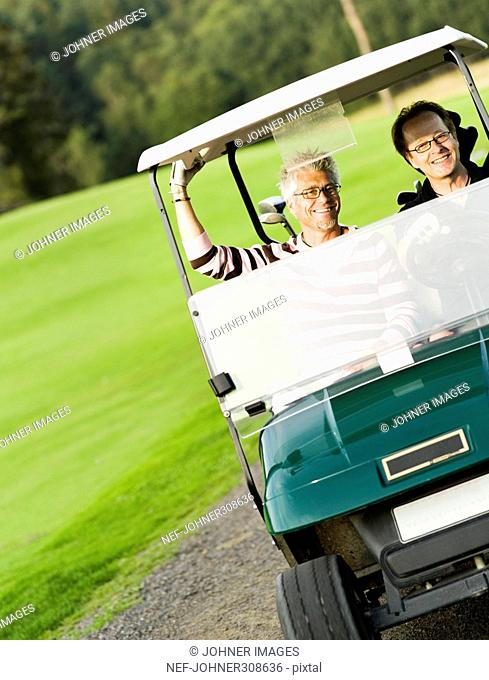 Two men in a golf car