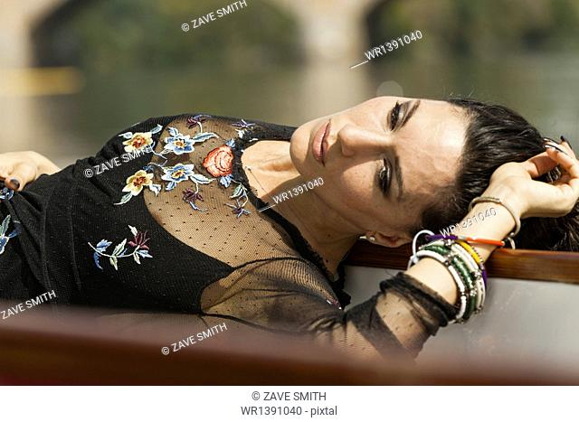 A woman lying on her back with her arm above her head. Wearing a fashionable black top with sheer sleeves, and embroidery. Bracelets on her arm