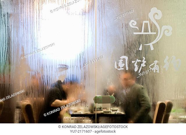 Two men in restaurant in Shanghai, China