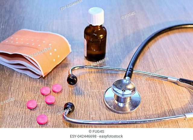 Stethoscope, pill and bandage on wooden background, medical concept