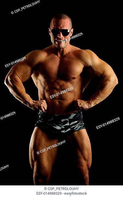Muscular man in sunglasses poses