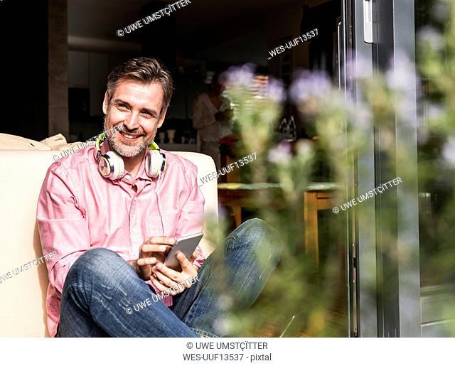Portrait of smiling mature man sitting at open terrace door using smartphone