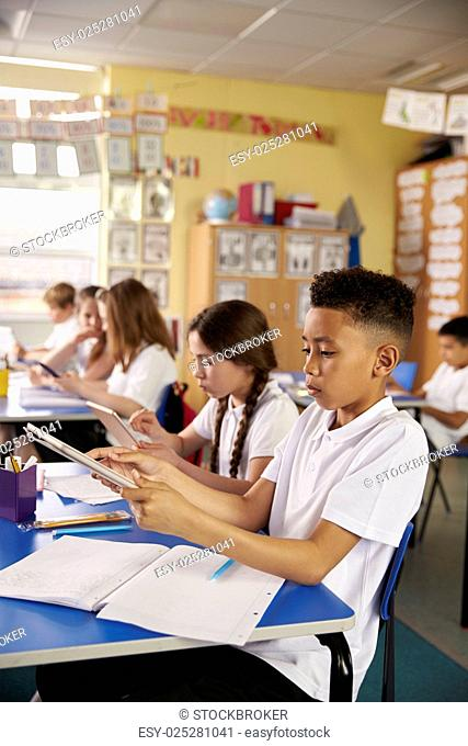 Kids use tablet computers in primary school class, vertical