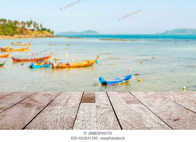 Wood table top on blurred blue sea and fishing boat with some people - Can be used for display or montage your products