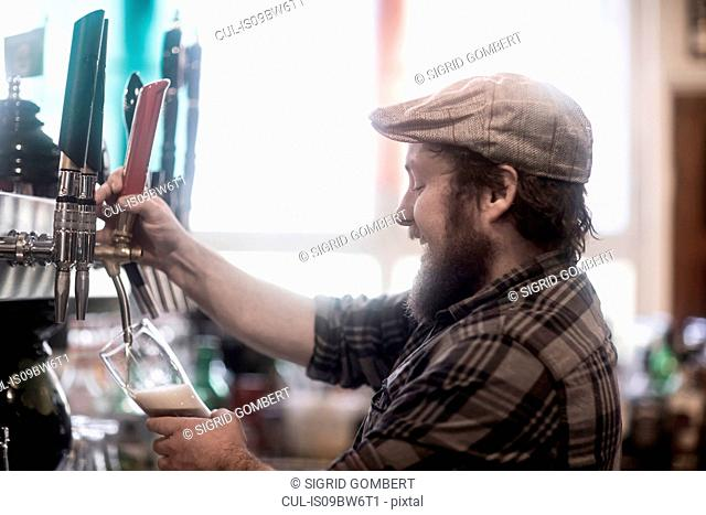 Barman pouring beer from pump in traditional Irish public house