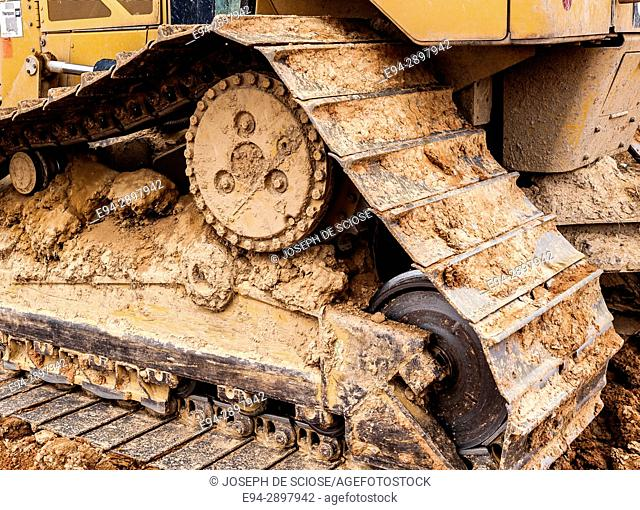 A partial view of a bulldozer showing the track roller coated in mud