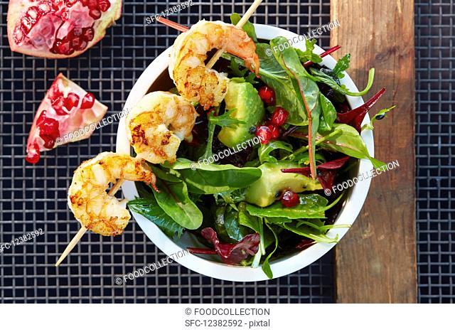 A prawn skewer on avocado salad with pomegranate seeds