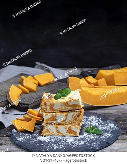 stack of square pieces of cottage cheese pie and fresh pumpkin, copy space