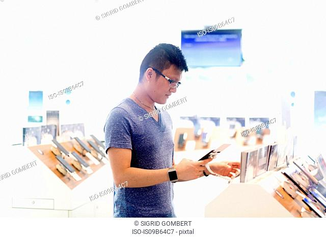 Man shopping in technology shop looking at smartphone