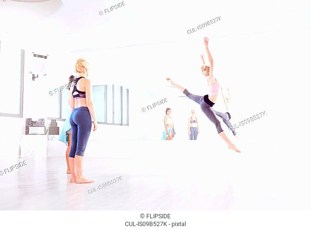 Young female ballet dancer practicing leaps in dance studio