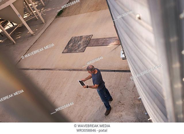 Man using digital tablet in factory