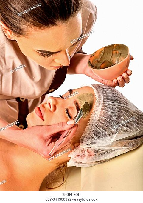 Mud facial mask of woman in spa salon. Massage with clay full face. Girl on with therapy room. Female lying wooden spa bed