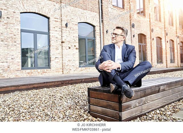 Businessman wearing blue suit sitting on bench