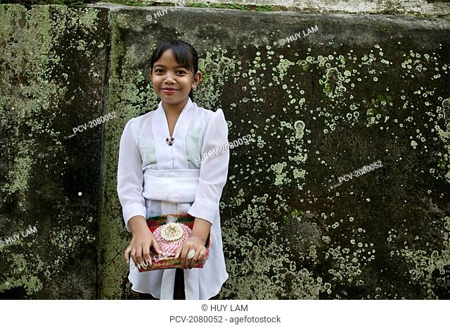 Young girl holding offerings for Kuningan Festival; Bali, Indonesia