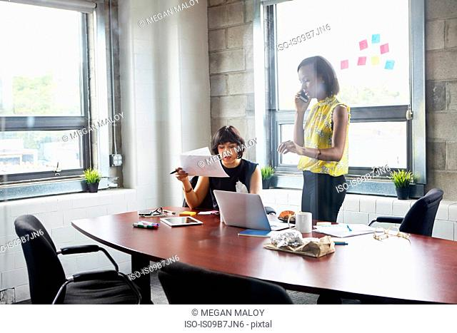 Two women working together in meeting room, brainstorming