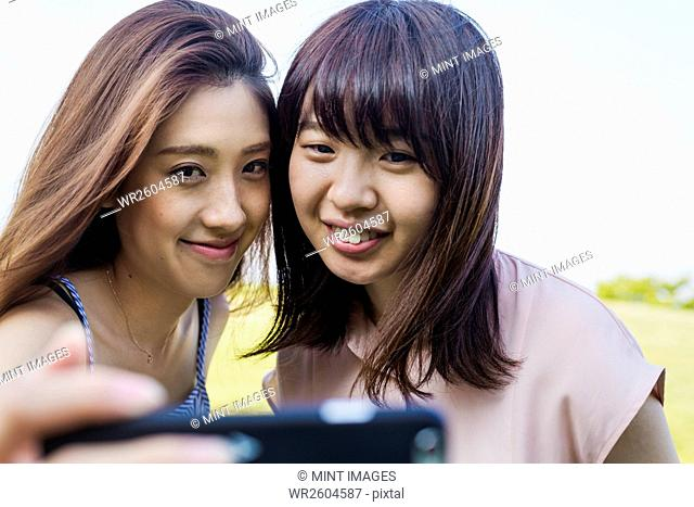 Two smiling young women with long brown hair, holding a mobile phone, taking selfie