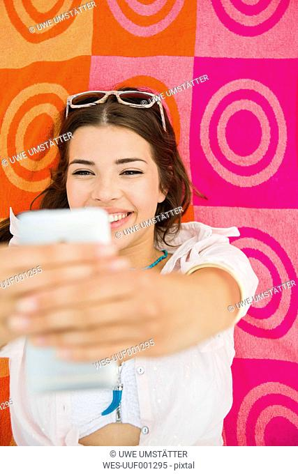 Portrait of smiling young woman lying on beach towel taking a selfie, elevated view