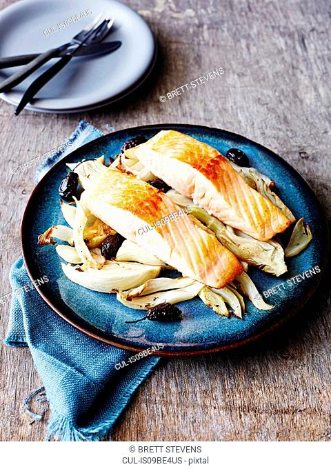 Baked salmon with fennel and olives, on blue plate, close-up