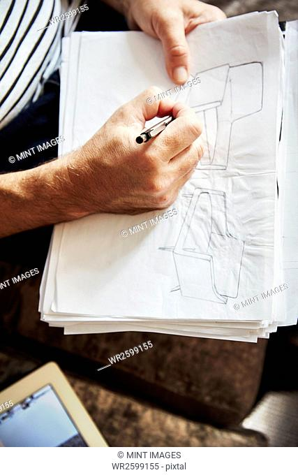 A man seated using a pen and drawing sketches, a designer at work