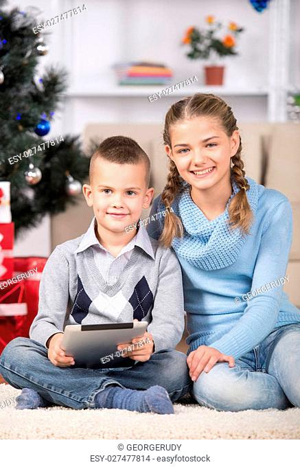 Cute girl and her brother with tablet are looking at camera. Christmas tree and gifts in background