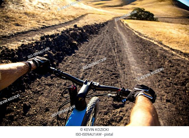Over the shoulder view man mountain biking on dirt track, Mount Diablo, Bay Area, California, USA