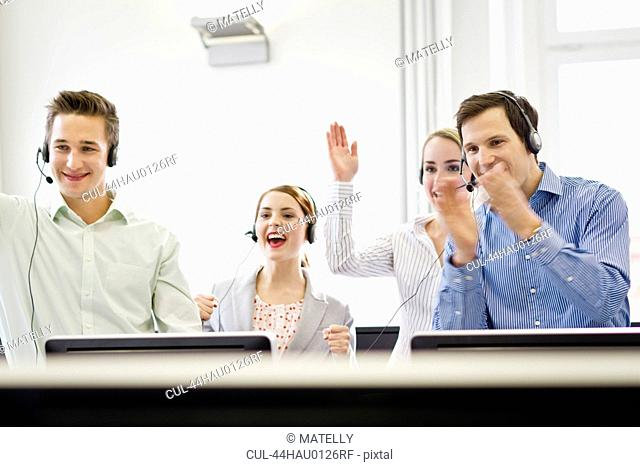 Business people cheering in headsets