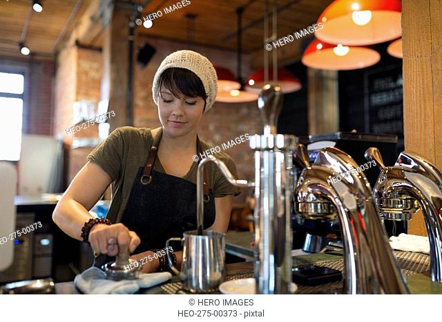 Barista pressing espresso with tamper in coffee shop