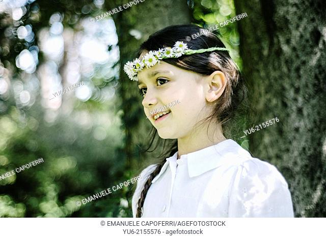Portrait of little girl with crown of daisies, smiles in the home garden