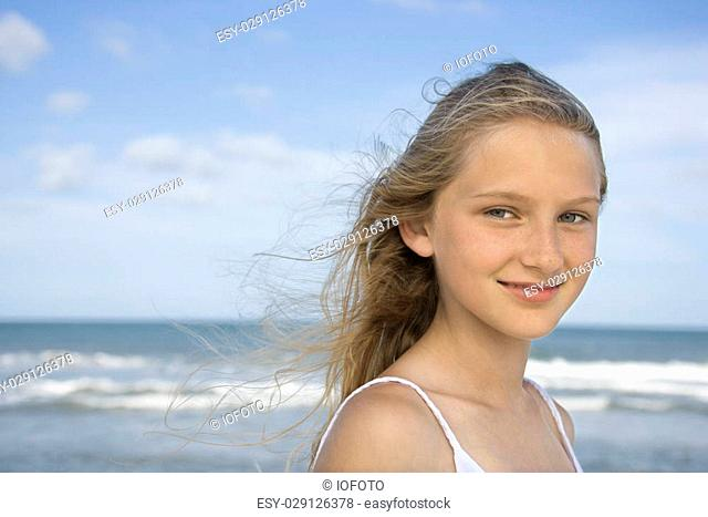 Caucasian pre-teen girl on beach looking at viewer
