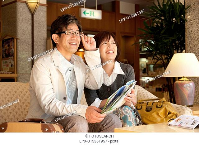 Mature Couple Sitting in Hotel Lobby and Planning Trip