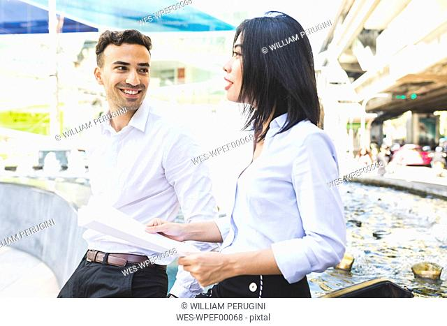 Thailand, Bangkok, smiling businessman and businesswoman with documents talking in the city