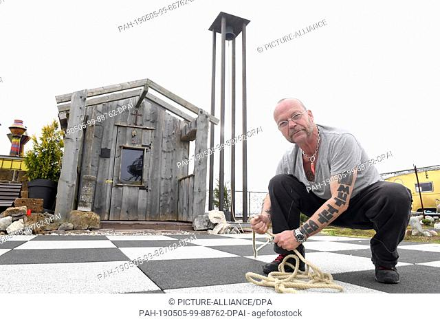 27 March 2019, Bavaria, Munich: Wolfgang Flatz, Austrian action artist, stage designer, musician and composer, sits on the roof of the Kistlerhof in front of a...