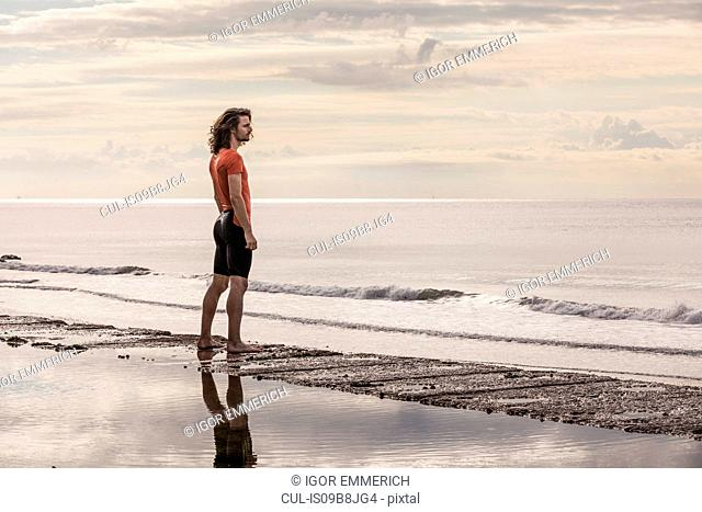 Man on shoreline looking away at view of sea