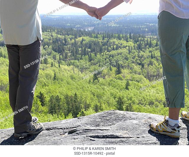Canada, Alberta, Hikers standing on rock holding hands