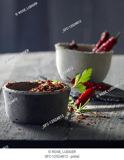 Chilli peppers in grey concrete bowls with parsley and rosemary