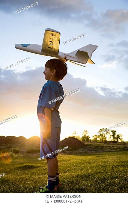 Boy (6-7) playing with model airplane outdoors