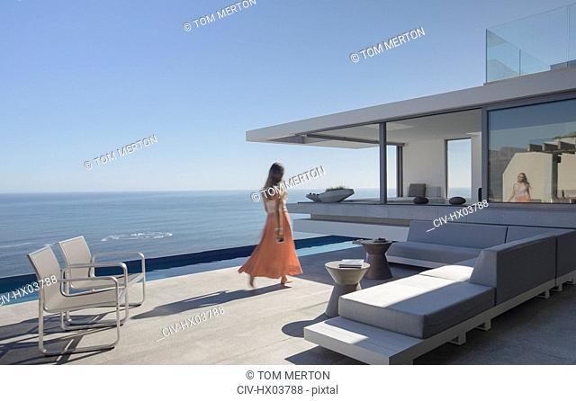Woman in dress walking on sunny, modern, luxury home showcase exterior patio with ocean view
