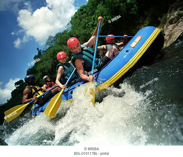 group of young people river rafting