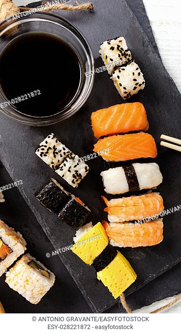 Black slate tray of assorted sushi and rolls