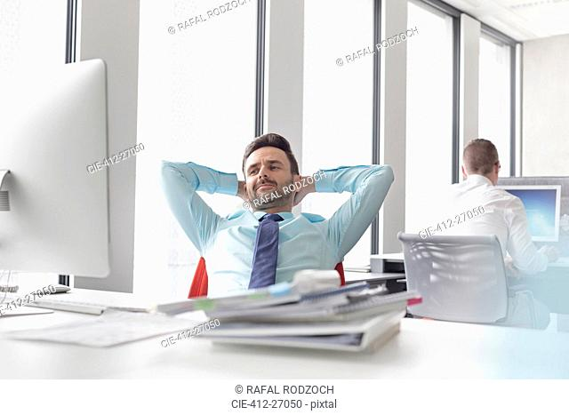 Relaxed businessman leaning with hands behind head at computer in office
