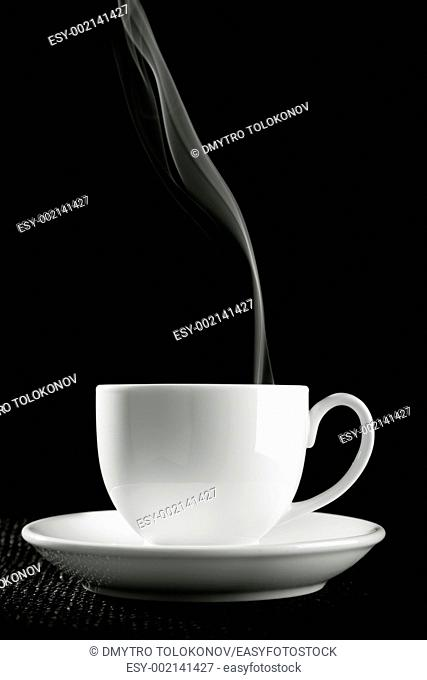 coffee cup over the table against black background