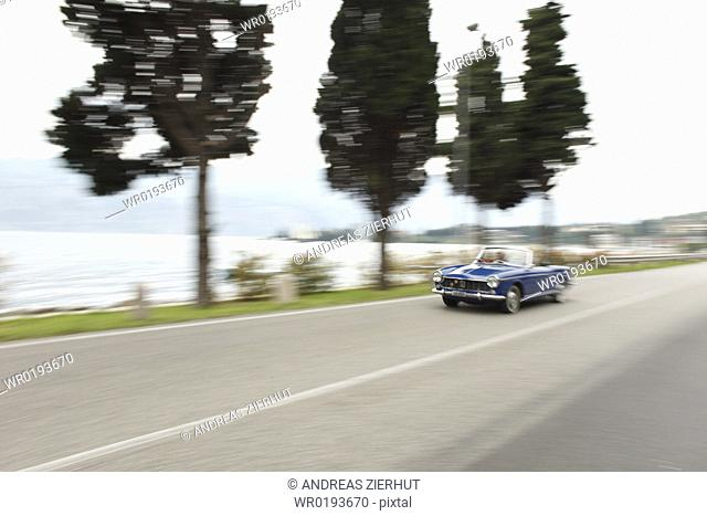 Senior couple driving convertible on coastal road, Italy