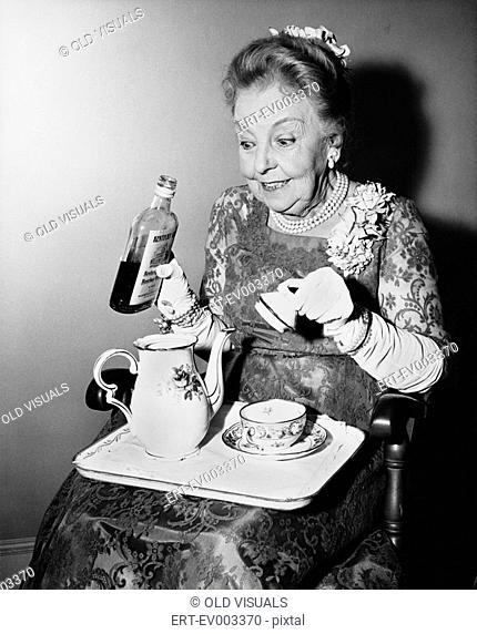 Elderly woman spiking her tea All persons depicted are not longer living and no estate exists Supplier warranties that there will be no model release issues