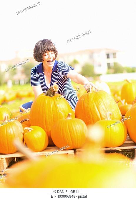 Mature woman picking up pumpkins